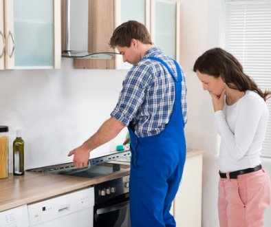Woman Looking At Worker Repairing Induction Hob